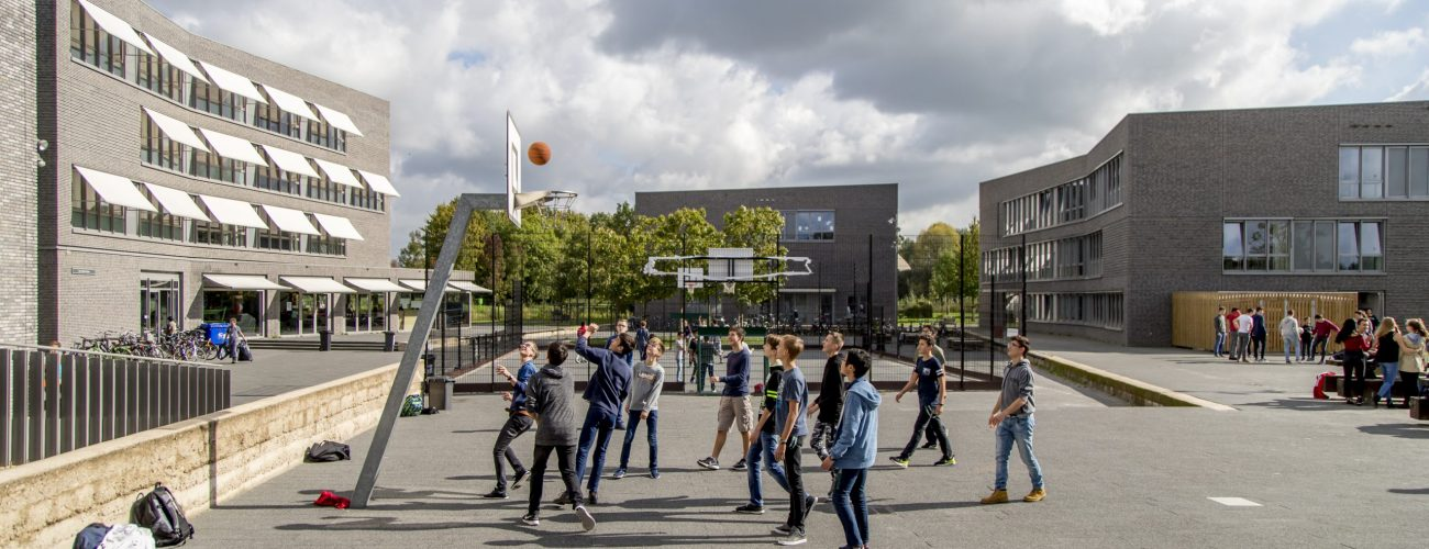 Kids playing basketball on campus